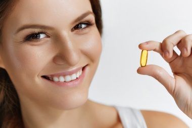 Vitamins. Healthy Eating. Close Up Of Happy Beautiful Girl With Pill With Cod Liver Oil Omega-3. Nutrition. Healthy Lifestyle. Nutritional Supplements. Sport, Diet Concept. Vitamin D, E, A Fish Oil Capsules.